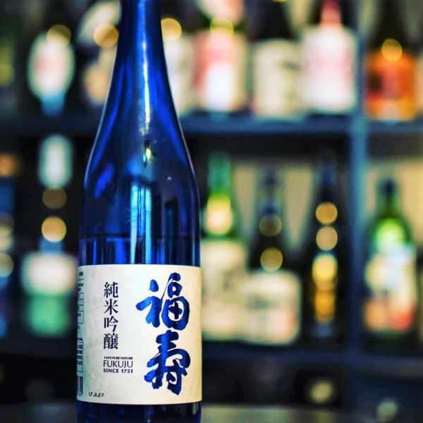 Ce label bleu Fukuju est un saké Junmai Ginjo (polissage de 60 %) élaboré à partir de riz provenant exclusivement de la préfecture de Hyôgo (la meilleure région productrice de riz à saké du Japon). La fermentation est effectuée à basse température pendant de longues périodes. Le bouquet rappelle celui de l'abricot mûr et présente une saveur douce d'umami de riz. C'est ce saké Label bleu Fukuju unanimement reconnu par les sommeliers du monde entier qui fut servi au banquet lors de la cérémonie de remise du prix Nobel pendant plusieurs années. La brasserie Fukuju qui élabore du saké depuis plus de 266 ans est située dans la région de Nada, à Kobe près du mont Rokko qui culmine à 931 m. Les ruisseaux coulant de la montagne lui fournissent une eau naturellement pure (miyamizu) avec le bon dosage en minéraux.