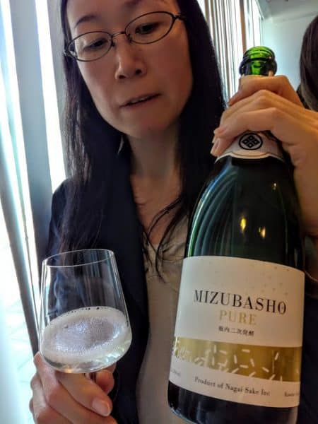 """Ce Mizubasho """"Pure"""" est un saké effervescent élaboré selon la méthode champenoise, un Junmaï Daïginjo, titrant 13° issu du riz yamada-nishiki de la préfecture de Gunma (l'une des huit préfectures sans littoral, la plus au nord-est de la plaine de Kantō). Elle est bordée par les préfectures de Niigata et Fokushima. Les bulles fines de ce saké aux notes de cerise et de litchi est une alternative au Champagne. Il s'accorde tout aussi bien à la cuisine asiatique qu'occidentale. La brasserie Nagaï Shuzo qui l'élabore est située à l'extrémité orientale des Alpes Japonaises, au pied du Mont Hotaka, dans le village de Kawaba-mura (la marque Mizubasho a été créée en 1992). Ici, à Paris, à la Maison de la culture du Japon en juin 2018 (Photo FC)"""